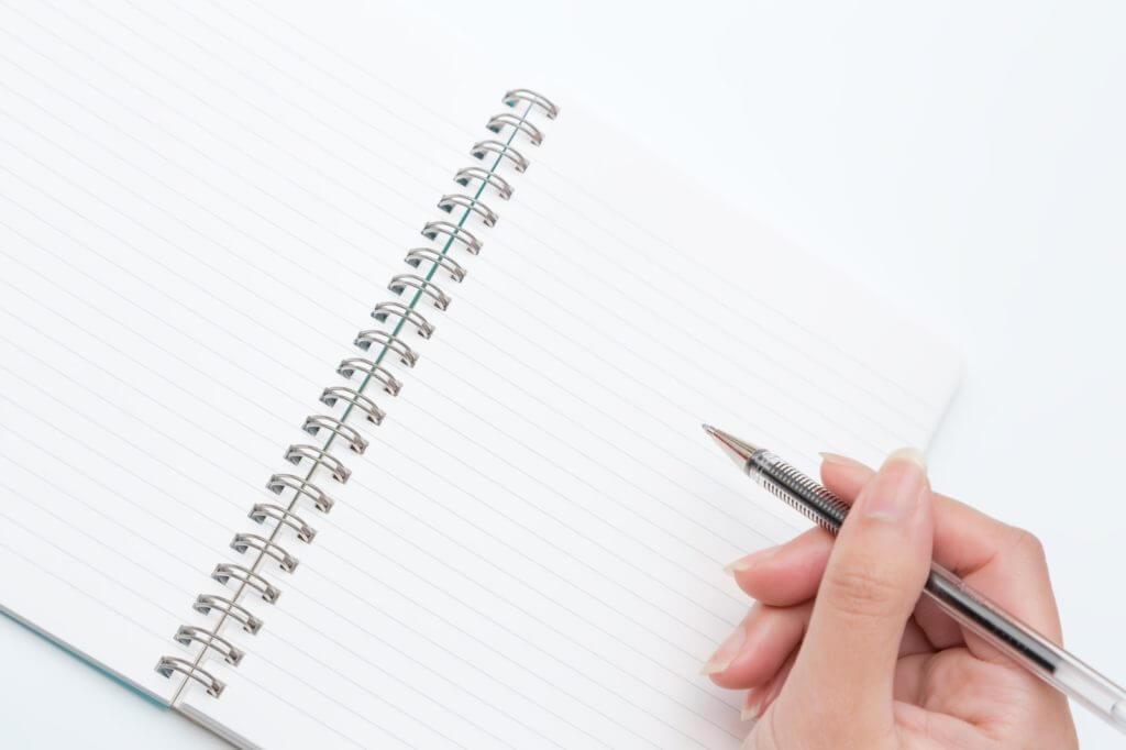 ペンを持つ手とノートペンを持つ手とノート